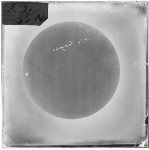 A photographic negative plate showing the dark circle of the sun with the small disc of Venus, 1874.